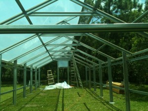 Metal greenhouse roofing being installed